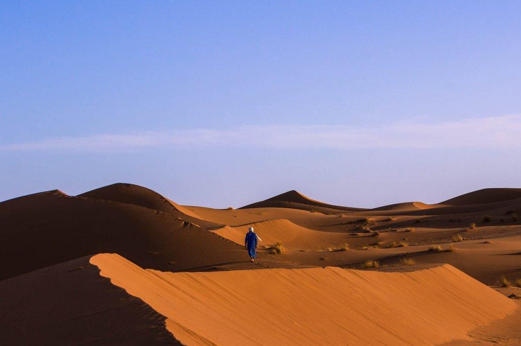 come andare nel deserto del Sahara: berbero cammina sulla duna