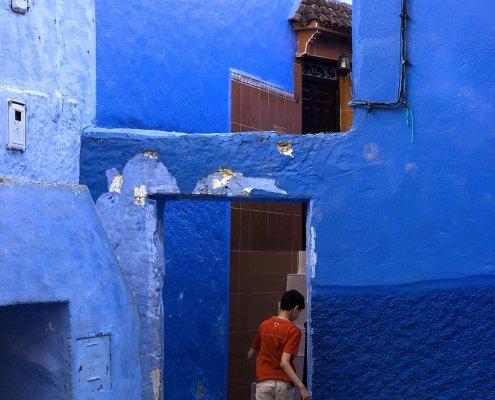 ragazzino gioca a calcio nella città blu del Marocco