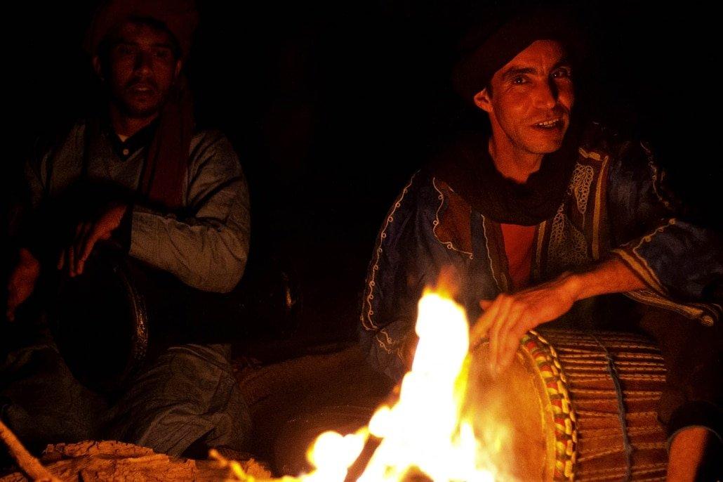 Musica del Marocco: due musicisti suonano nel deserto intorno a un falò
